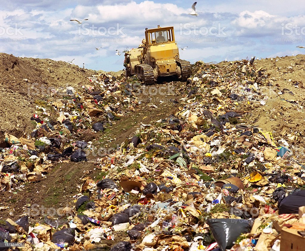 A bulldozer driving up a hill of garbage stock photo