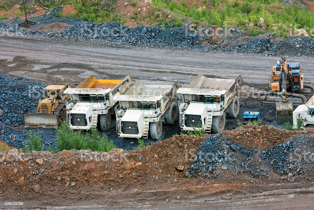 Bulldozer, dump trucks and excavator at the bottom of the quarry royalty-free stock photo