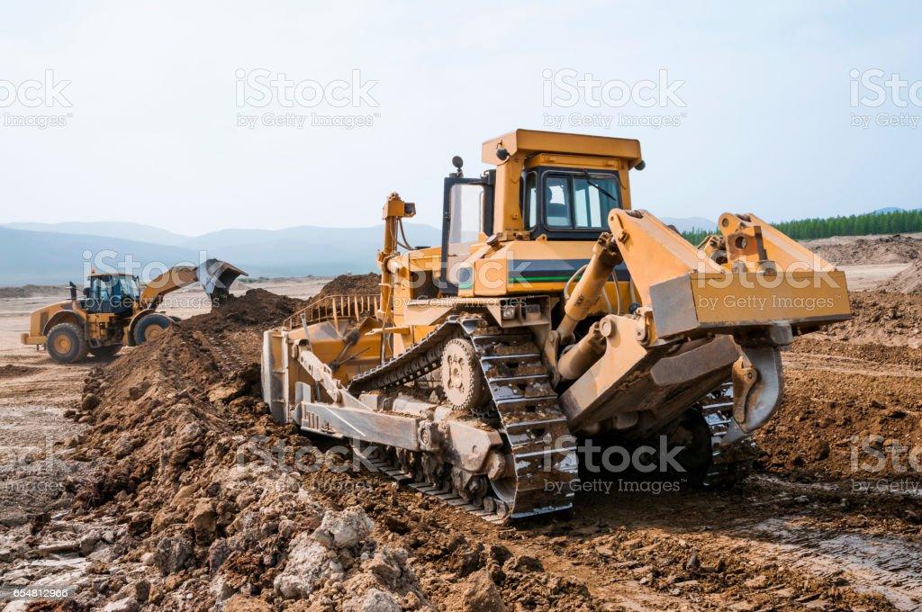 Bulldozer in open field operation stock photo