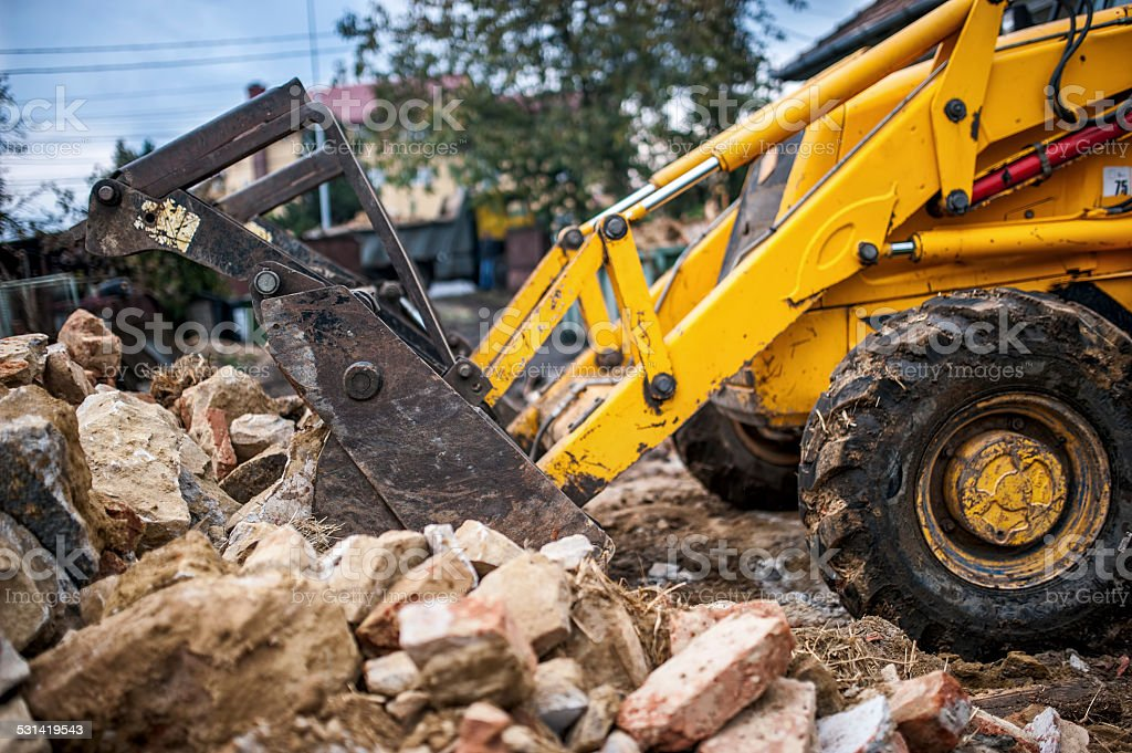 bulldozer loading demolition debris and concrete for recycling at construction stock photo