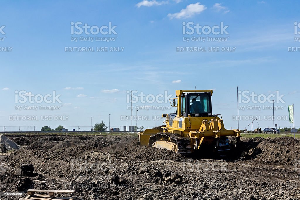Bulldozer machine is leveling construction site stock photo