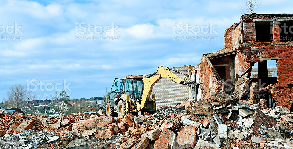Bulldozer on a building site is breaking old brick building stock photo