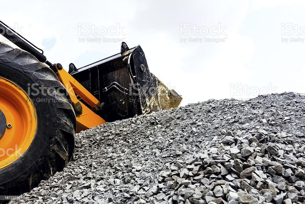 Bulldozer picking up gravel on jobsite. royalty-free stock photo