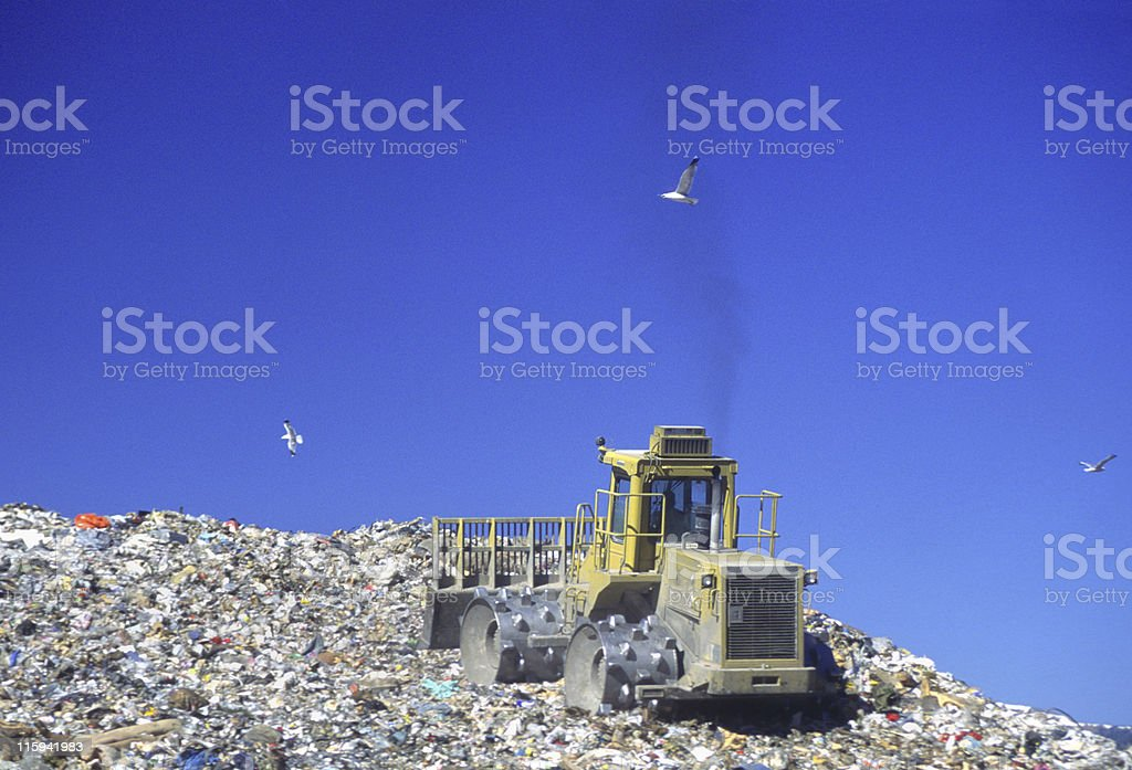 A bulldozer pushing trash in a landfill stock photo