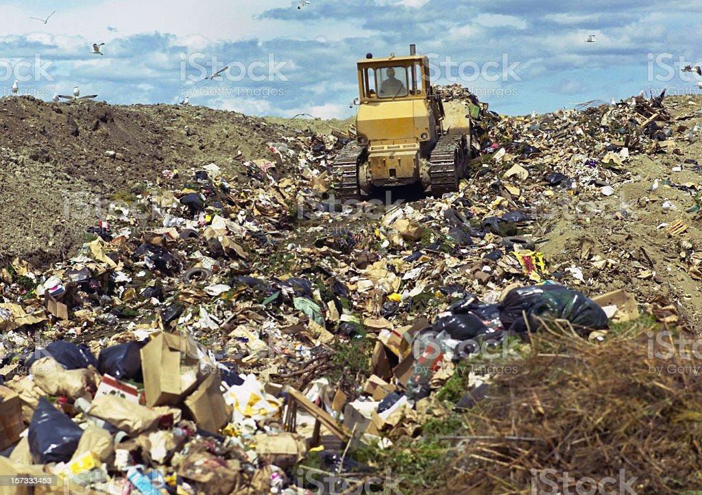 Bulldozer pushing trash in landfill stock photo