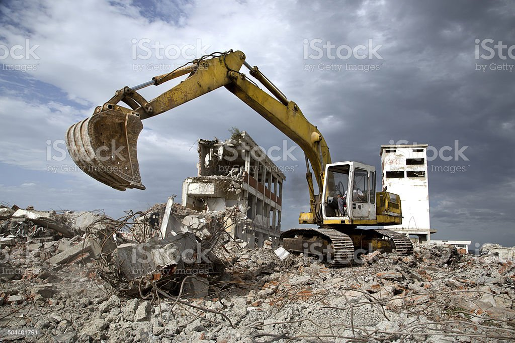 Bulldozer removes the debris from demolition of old derelict buildings stock photo