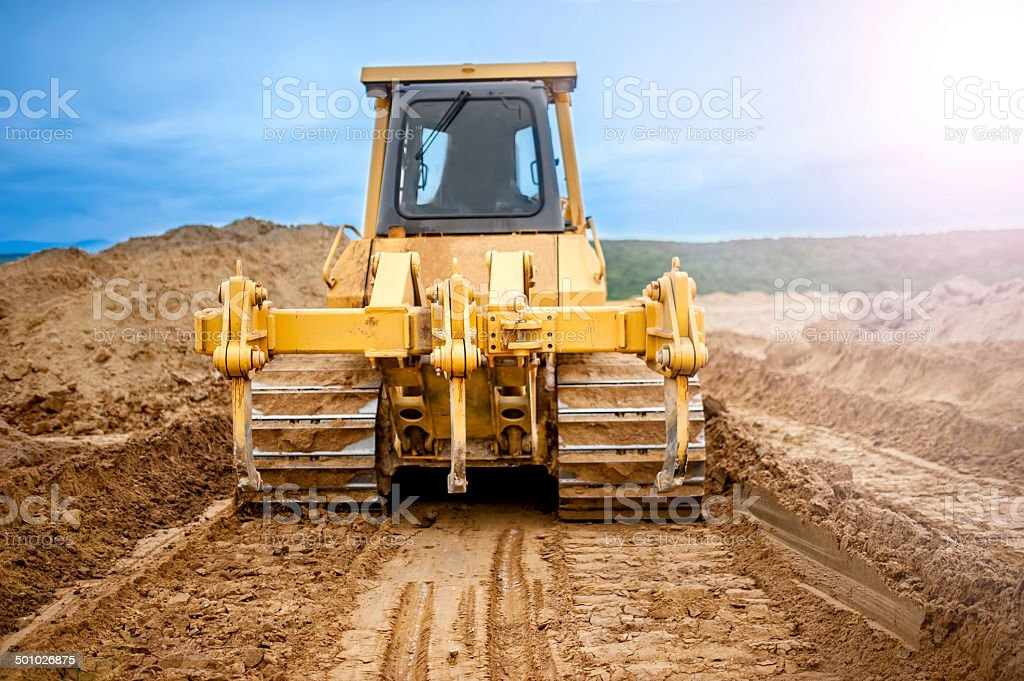 Bulldozer with steel blade moving soil and sand around stock photo