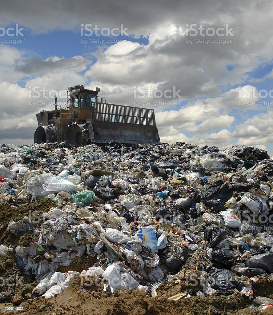 Bulldozer working on top of a garbage dump stock photo