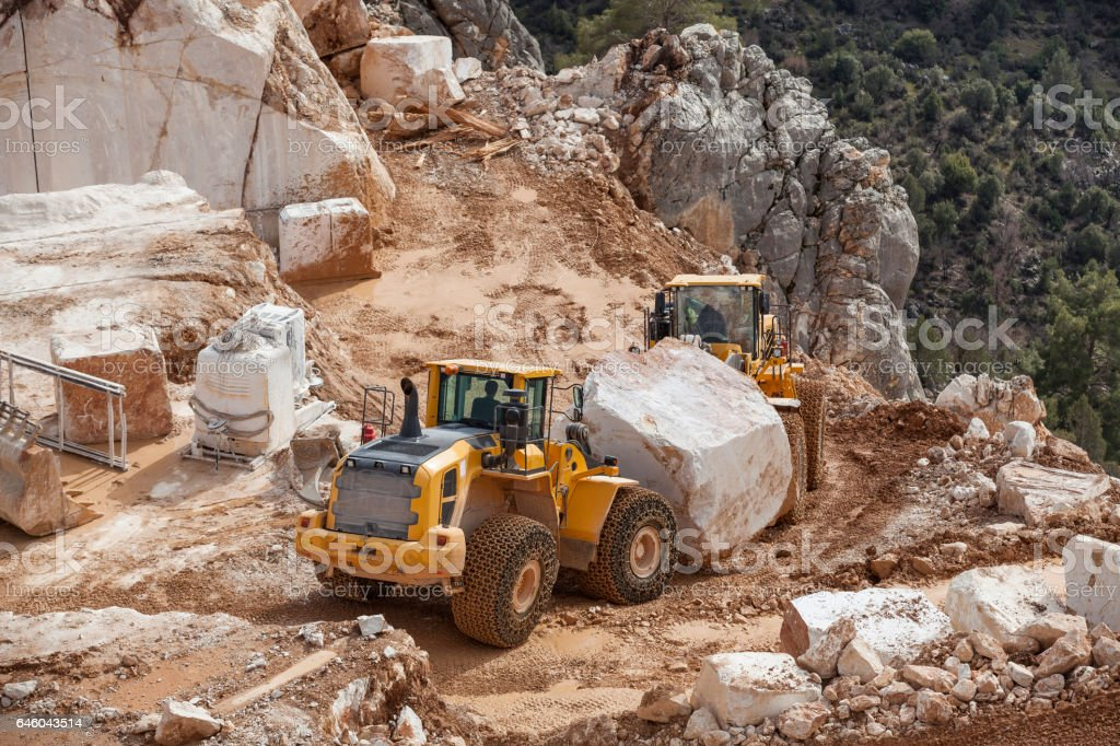 Bulldozers carrying oversized marble block in Quarry stock photo