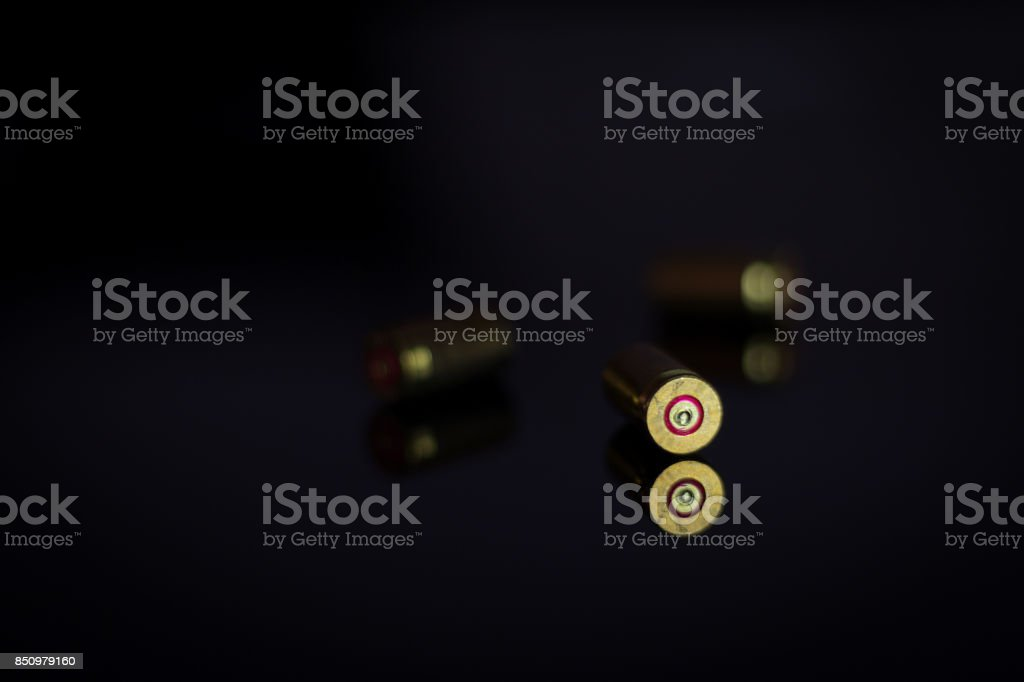 Bullet casings  in shadow on a glass table stock photo