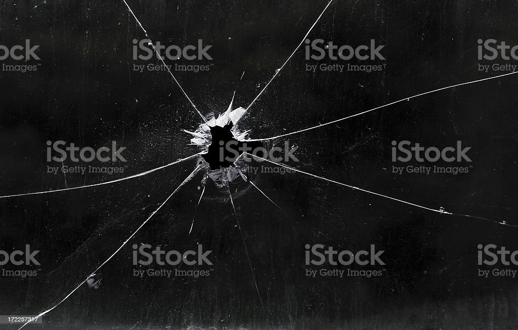 A bullet hole in a glass window stock photo