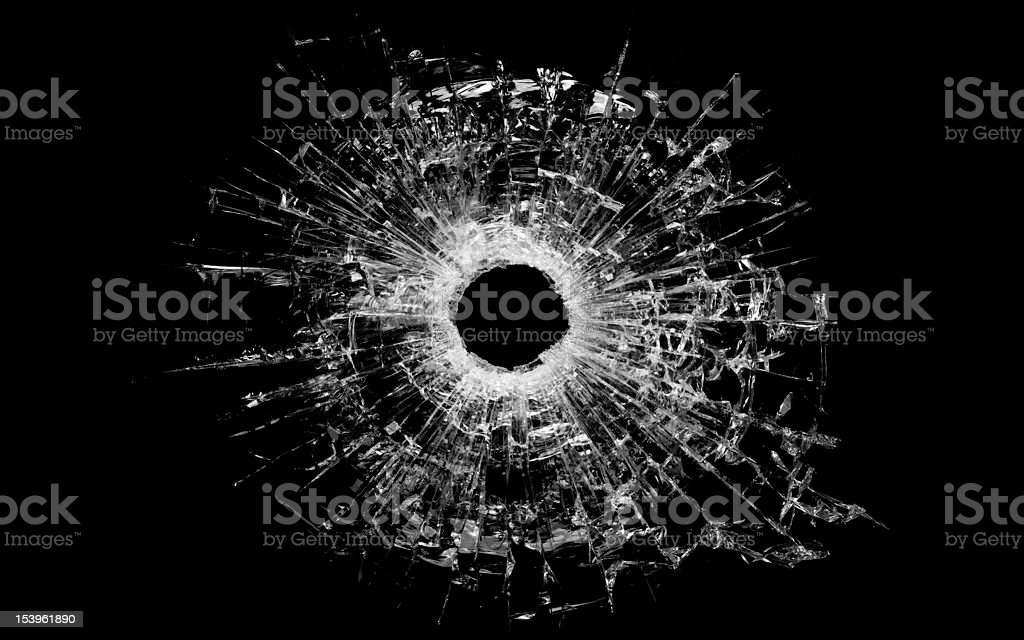 bullet hole in glass isolated on black stock photo
