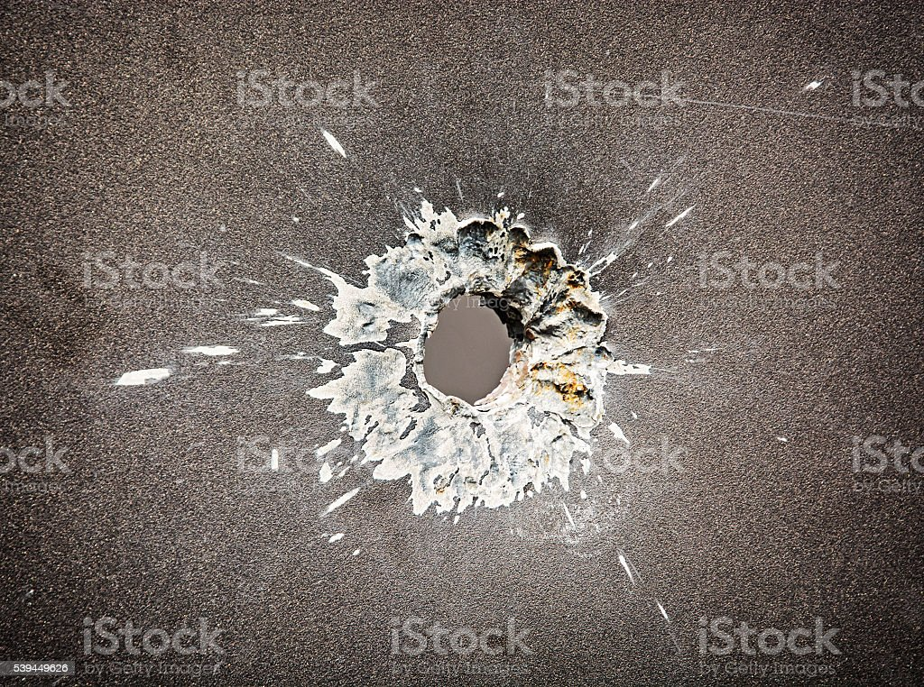 Bullet hole in the metal plate stock photo