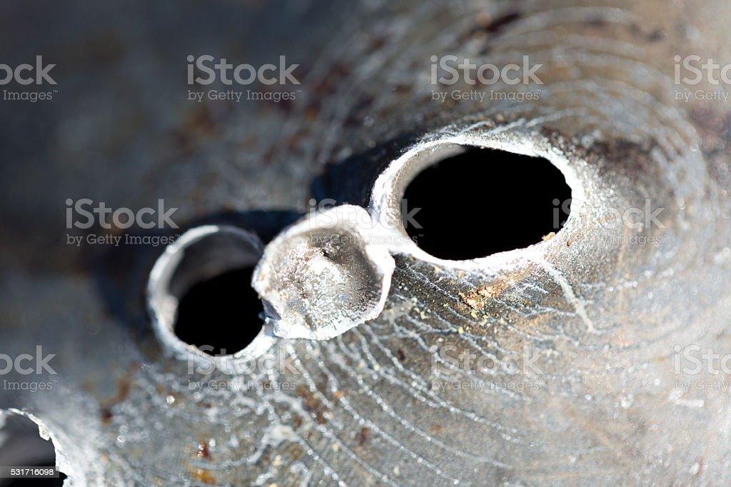 Macro shot of bullet holes in a aluminum pan.