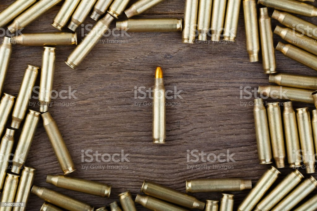 M-16 bullet on wooden table close-up. stock photo