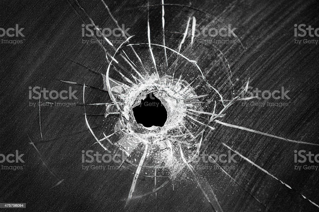 Bullet shot cracked hole on broken window glass stock photo