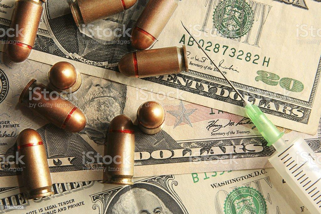 Bullets and syringe with needle on dollars background stock photo