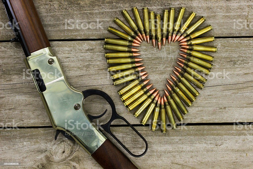 Bullets in the shape of heart next to rifle stock photo