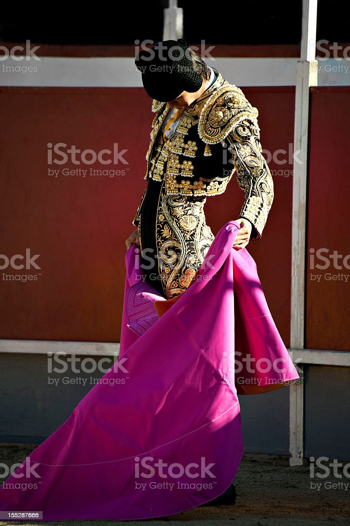 Bullfighter in full costume over a white and red background stock photo