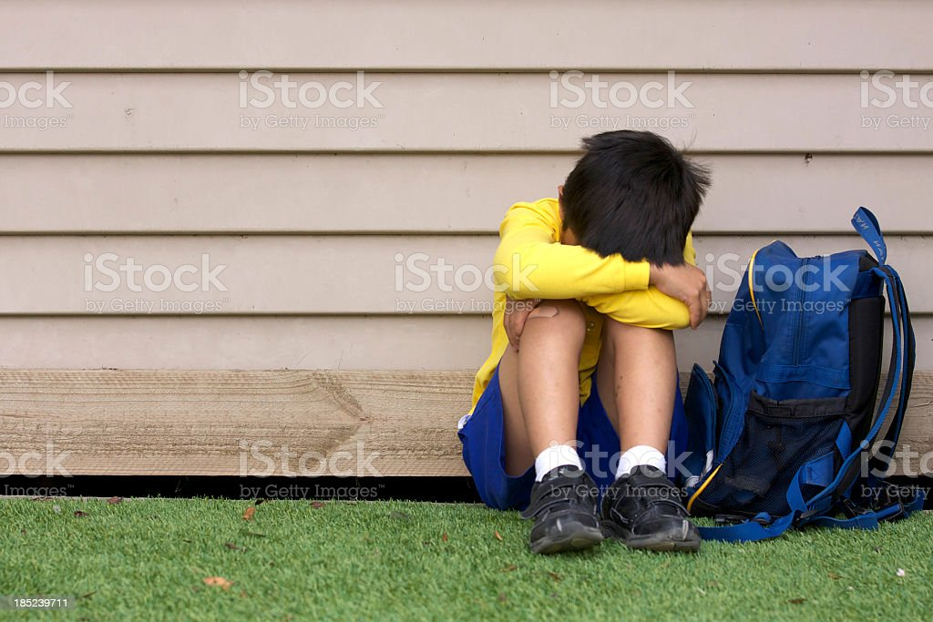 Bullied young boy sitting on grass with his head in his lap royalty-free stock photo