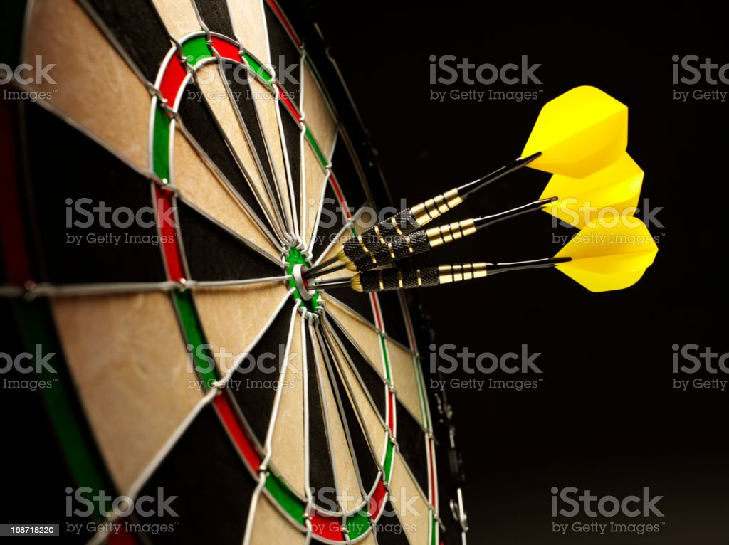Bulls Eye in a Dartboard with Yellow Darts stock photo