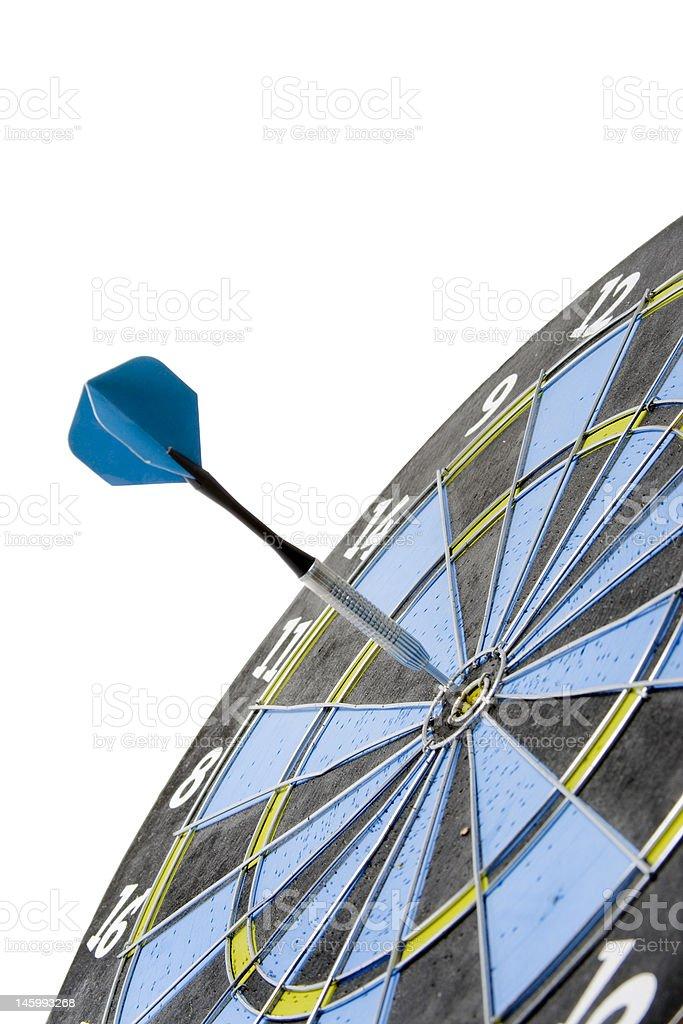 Dart in dart board, hitting the bullseye, on white.