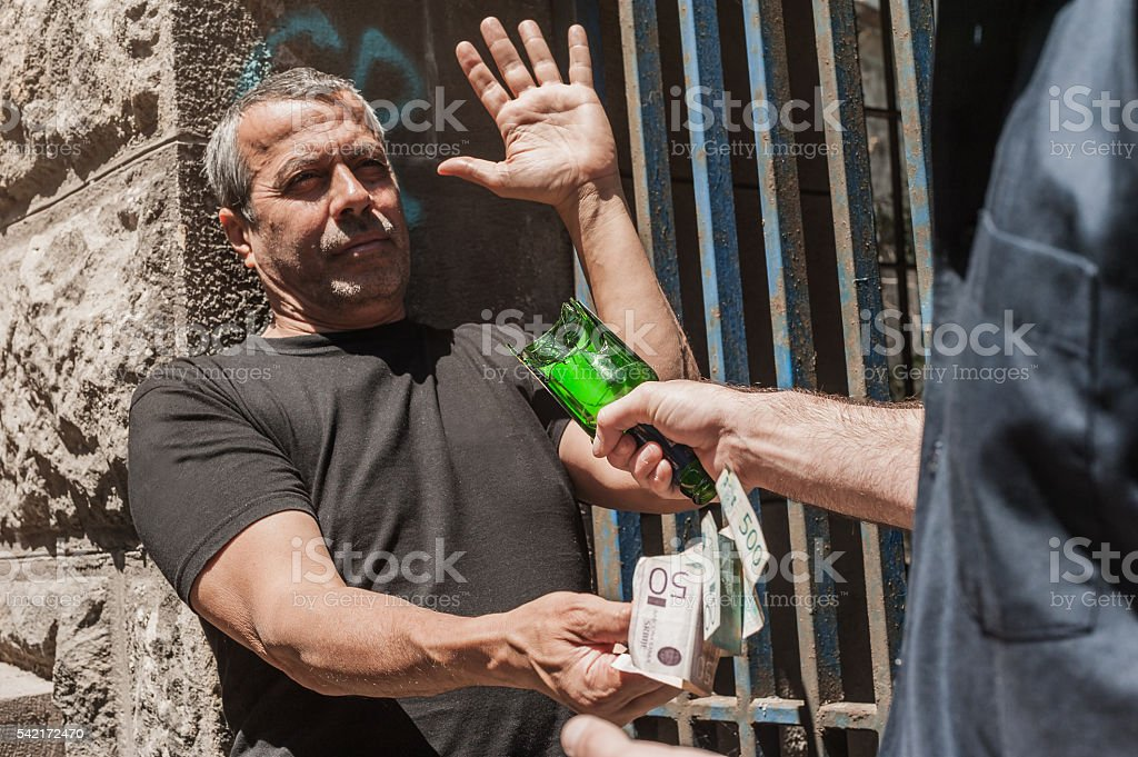 Bully with a broken bottle taking money from victim stock photo