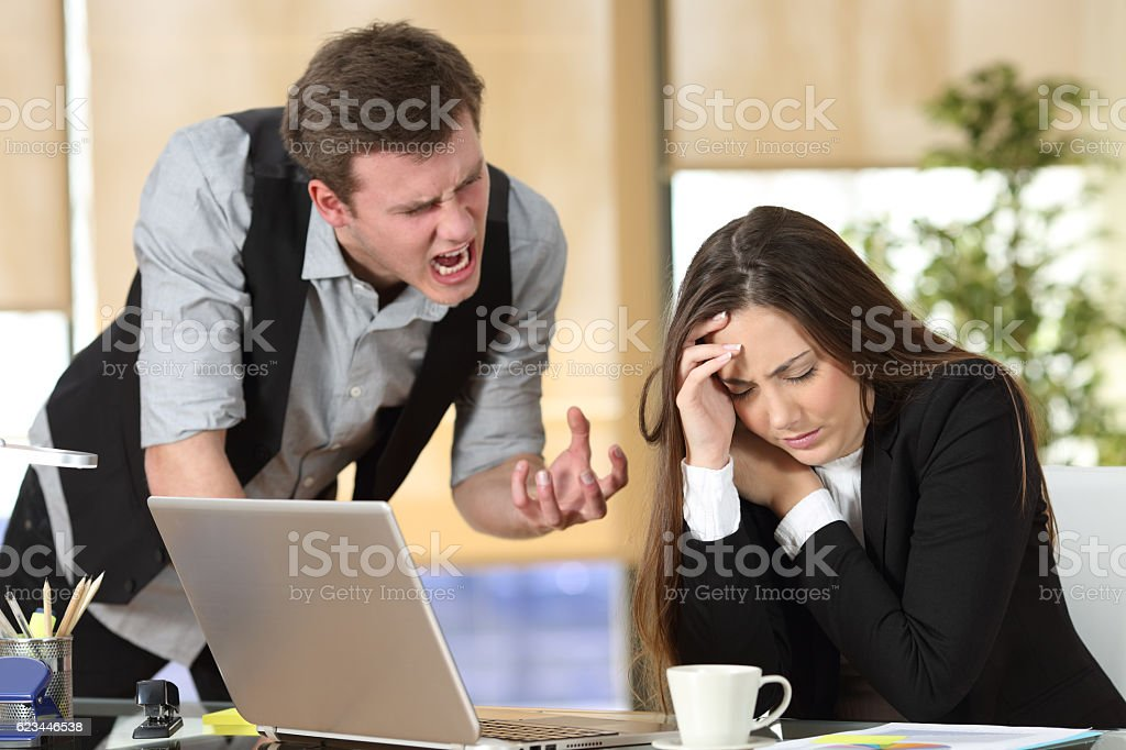 Bullying with a boss shouting to an employee stock photo