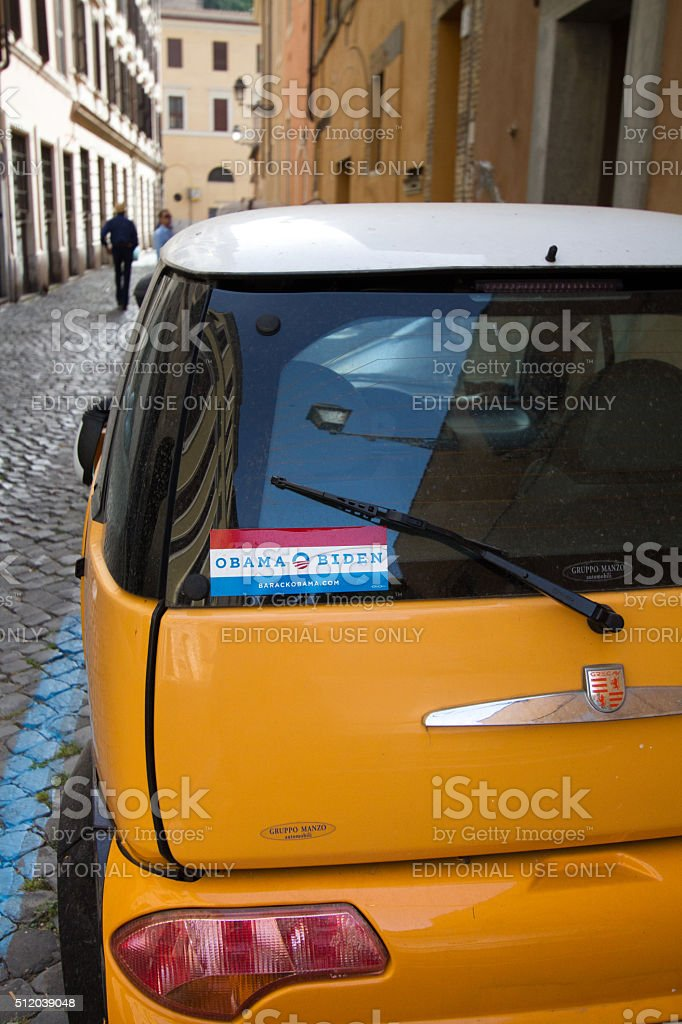 OBAMA-BIDEN Bumper Sticker on Little Yellow Car, Cobbled Street, Rome stock photo