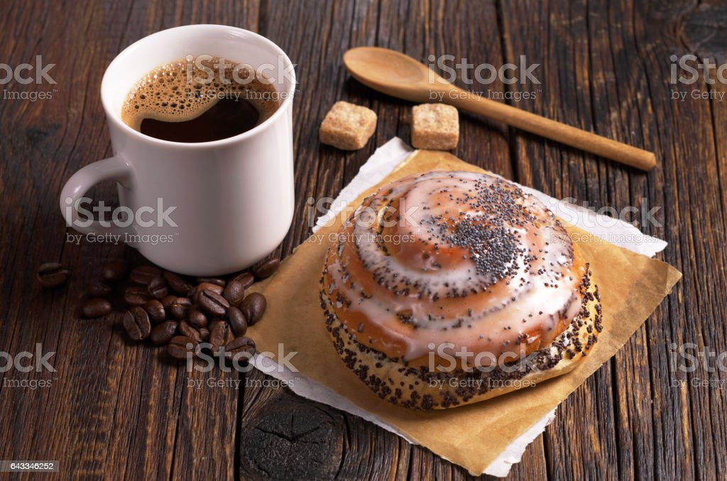 Buns with poppy seeds and cup of hot coffee on dark wooden table