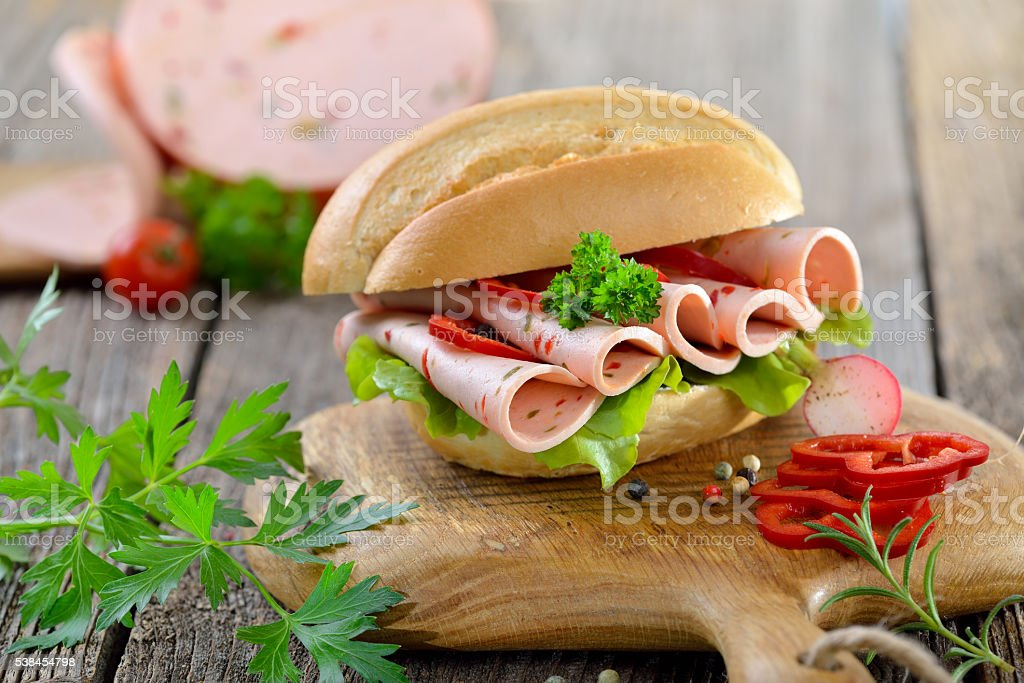 Bun with sliced sausage stock photo