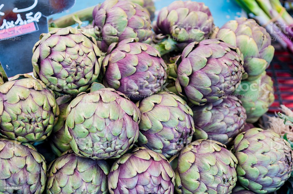 Bunch of artichokes sold in Udine market stall stock photo