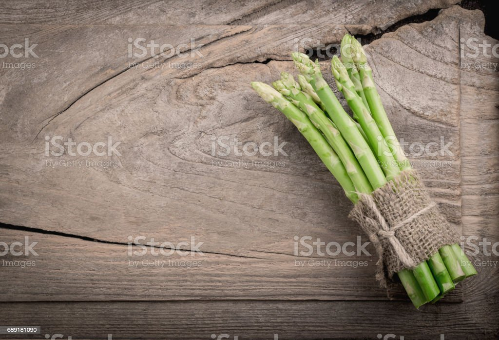 bunch of asparagus stems on brown wooden table. stock photo