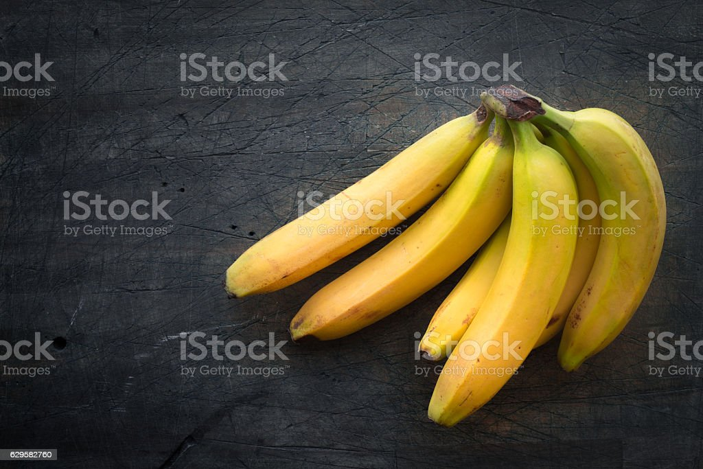 Bunch of bananas on the dark scratched table top view stock photo