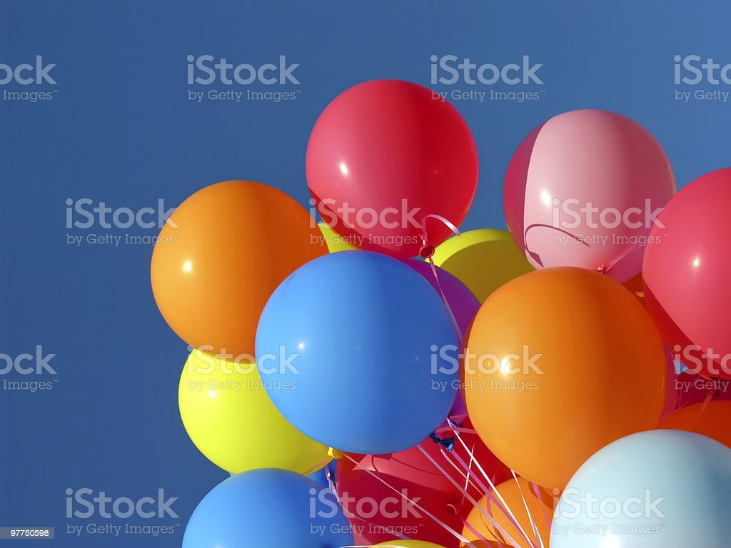 Bunch of bright colored balloons on ribbon against blue sky stock photo