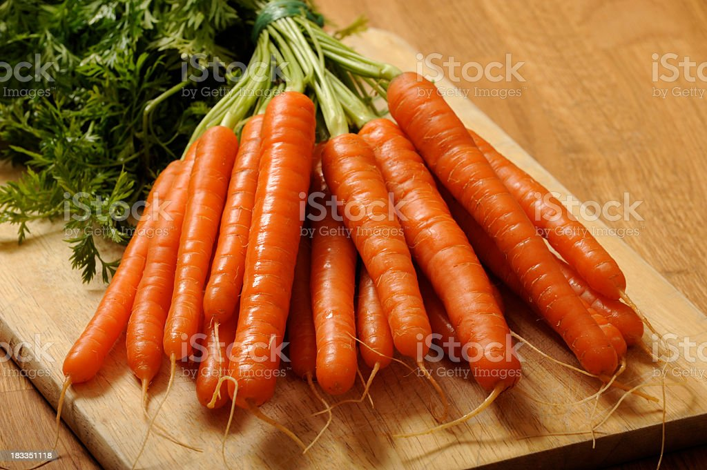 Bunch of carrots on wooden board royalty-free stock photo