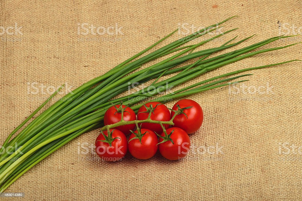 Bunch of cherry tomato and spring onion shots at canvas royalty-free stock photo