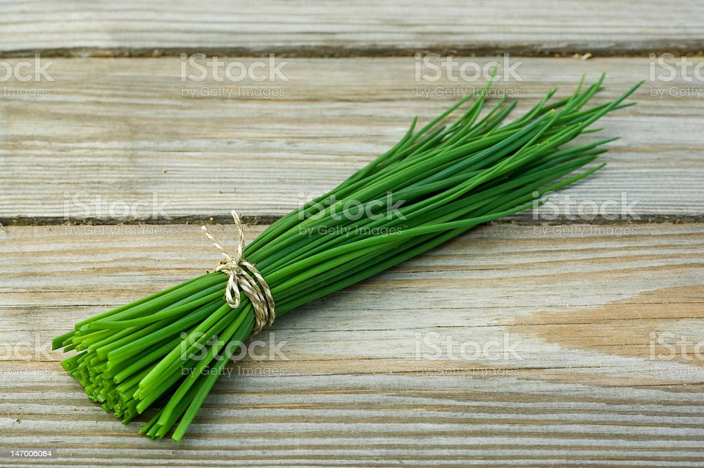 Bunch of chives tied with twine on wooden table stock photo