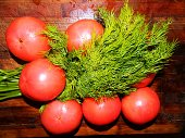 Bunch of dill beam and fresh red tomato