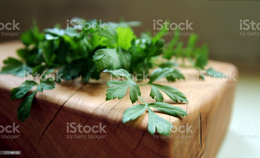 Bunch of Flat Leaf Parsley Lying on a Cutting Block royalty-free stock photo