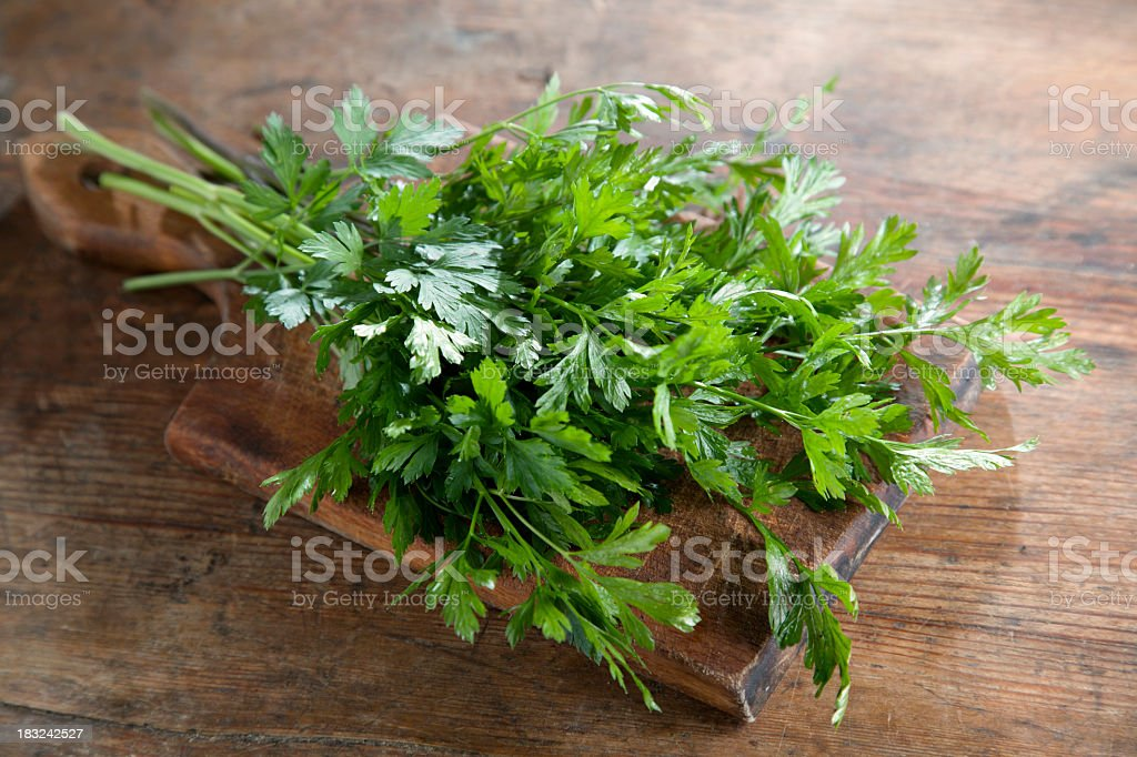 A bunch of flat leaved parsley on a wooden board stock photo