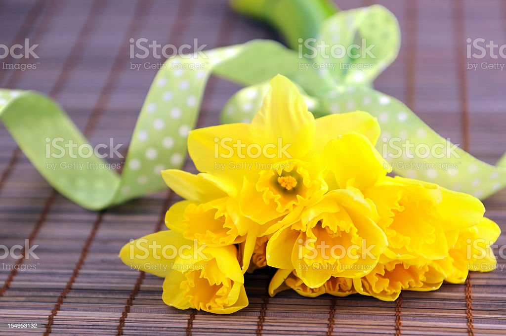 bunch of flower with yellow daffodil and green ribbon stock photo