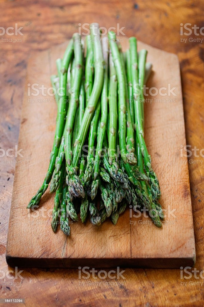 A bunch of fresh asparagus on a wooden cutting board & table royalty-free stock photo