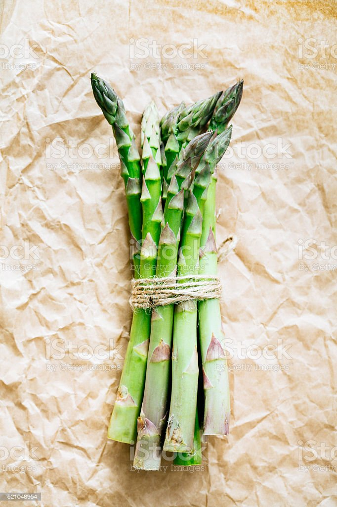 Bunch of fresh asparagus on the kraft paper stock photo