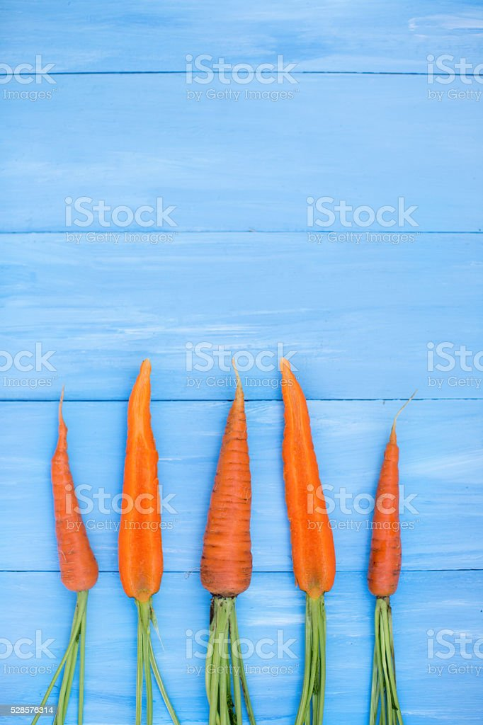Bunch of fresh carrots on blue table. stock photo