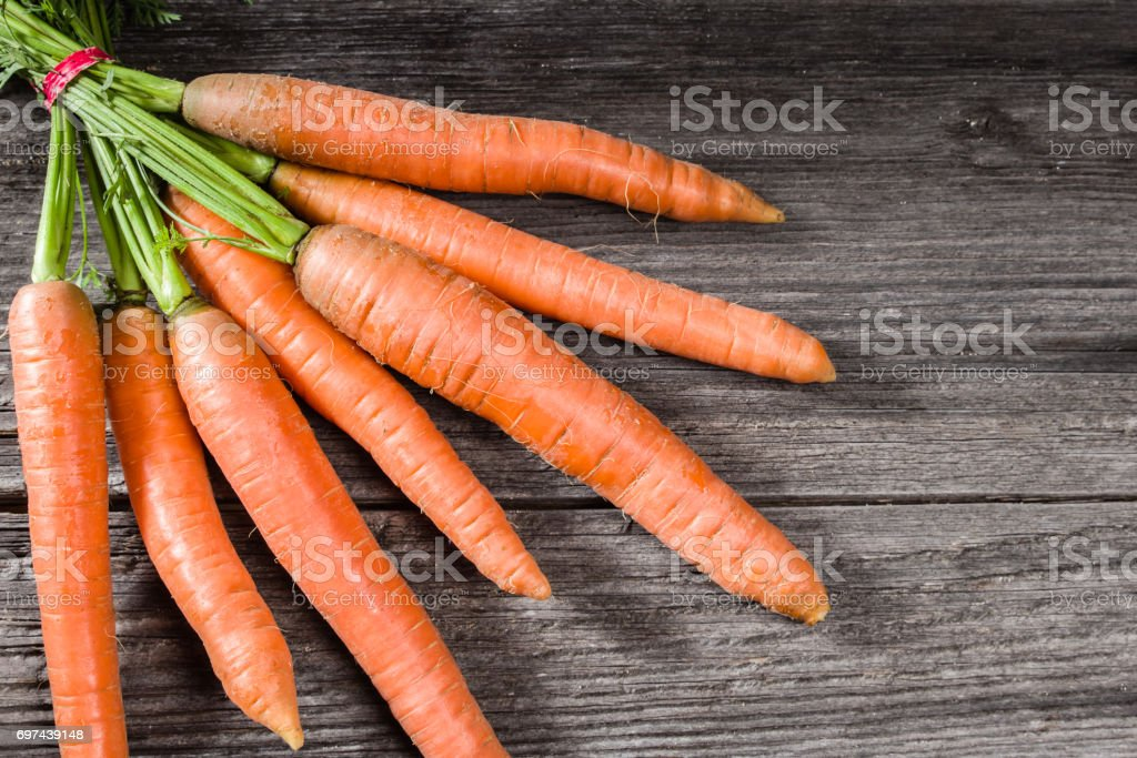 Bunch of fresh carrots on wooden table stock photo