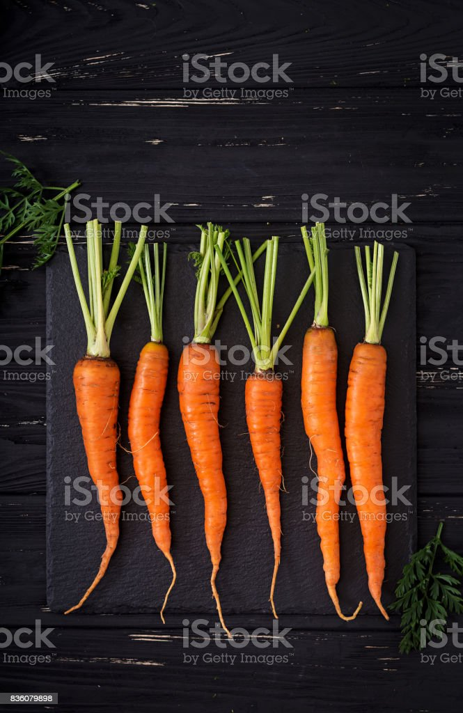 Bunch of fresh carrots with green leaves on  dark  wooden background. Flat lay. Top view stock photo
