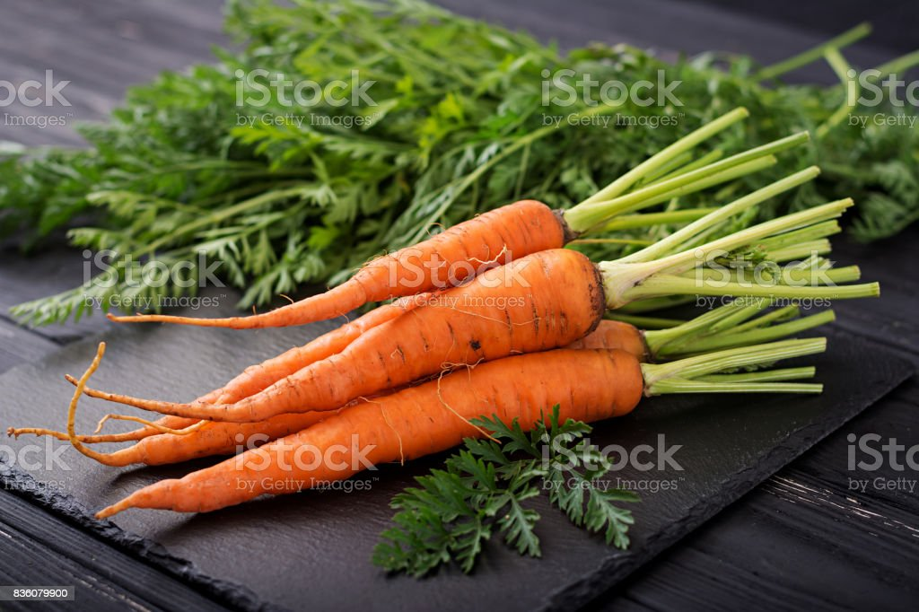 Bunch of fresh carrots with green leaves on  dark  wooden background. stock photo