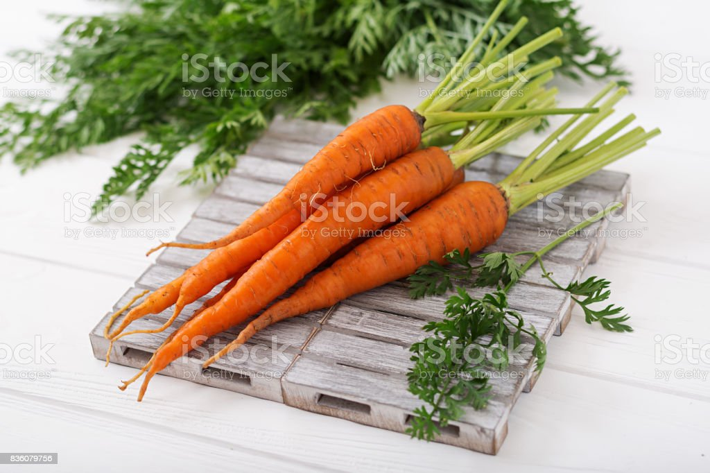 Bunch of fresh carrots with green leaves on  light  wooden background stock photo
