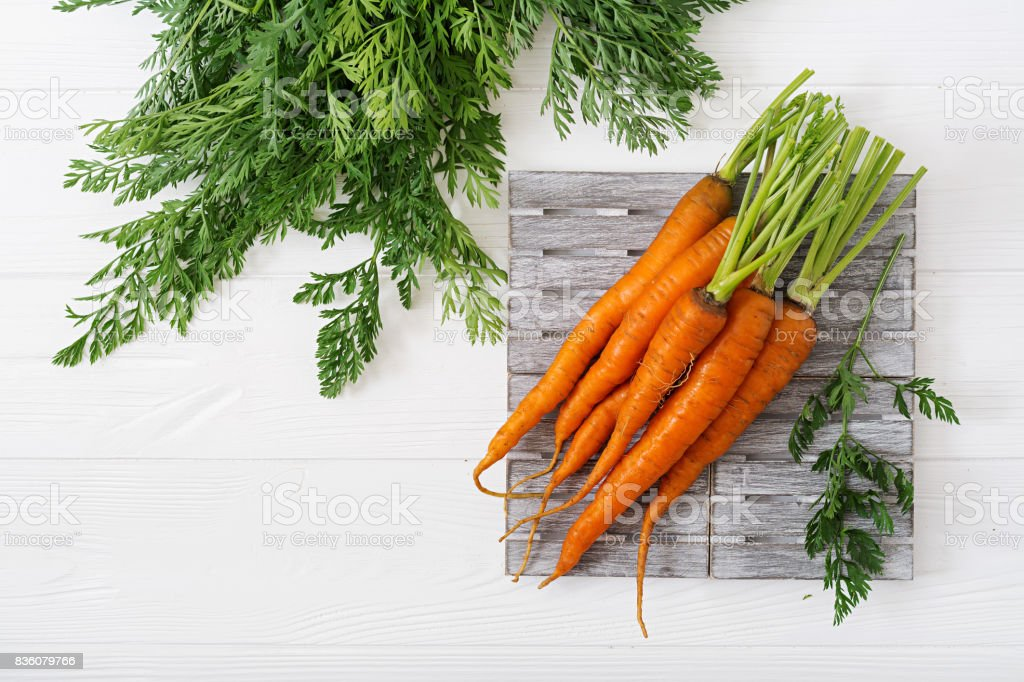 Bunch of fresh carrots with green leaves on  light  wooden background. Flat lay. Top view stock photo